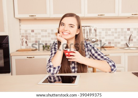 Cheerful young girl drinking coffee in the kitchen with tablet - stock photo