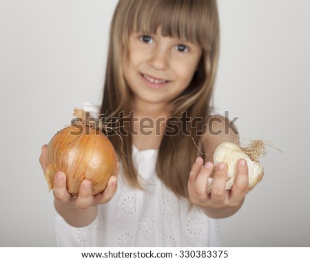 cheerful young girl holding onions - stock photo