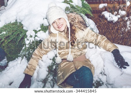 cheerful young girl in a woolen hat and yellow jacket sitting in snow in winter evening forest - stock photo