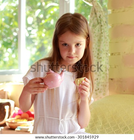 Cheerful young girl in his room playing with toys and smiling - stock photo