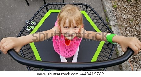cheerful young girl jumping on trampoline - stock photo