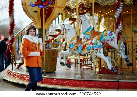 Cheerful young girl on a Christmas market in Paris, near a traditional French merry-go-round - stock photo
