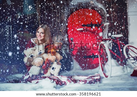 Cheerful young girl sitting on the snow. In the hands holding a teddy bear. The sun is shining and it is snowing - stock photo
