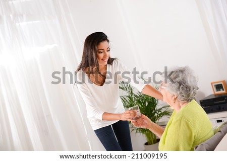 cheerful young girl taking care of an elderly woman at home - stock photo