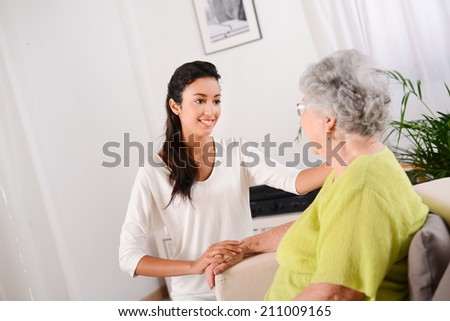 cheerful young girl taking care of elderly woman at home - stock photo
