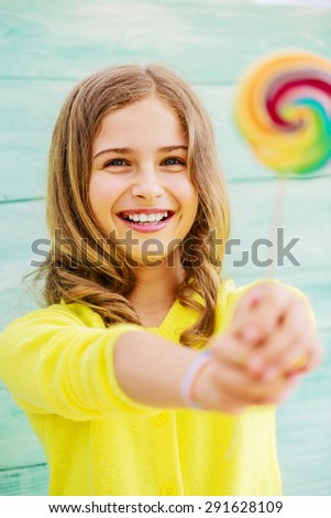 Cheerful young girl with a lollipop - stock photo