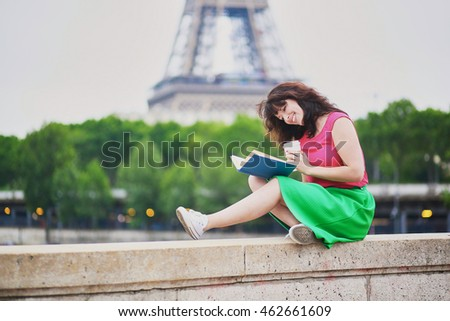 Cheerful young girl with coffee to go reading a book near the Eiffel tower. Student preparing for exam in Paris. International education exchange program in France concept