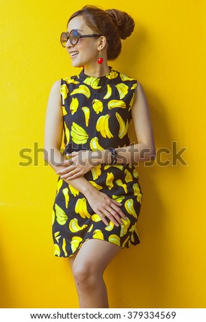 Cheerful young girl, with dark hair, wearing in blue dress and black sunglasses, is posing , on Yellow background, in studio, waist up   - stock photo