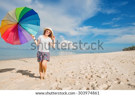Cheerful young girl with rainbow umbrella having fun on sunny day on the beach with beautiful ocean and blue sky on background.Travel, holidays, vacation, healthy lifestyle concept - stock photo