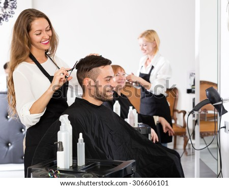 Cheerful young guy cuts hair at the hair salon - stock photo