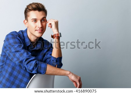 Cheerful young guy is dreaming with joy - stock photo