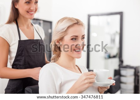 Cheerful young hairdresser is braiding female hair. She is standing in apron at beauty salon. The woman is sitting and drinking tea. They are smiling happily - stock photo