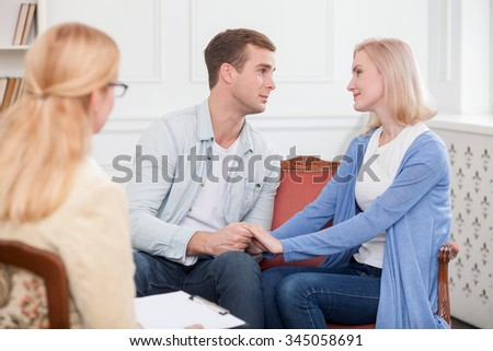 Cheerful young husband and wife are solving problems with the help of psychologist. They are sitting and smiling. The man is looking at the woman with love. They are holding hands - stock photo