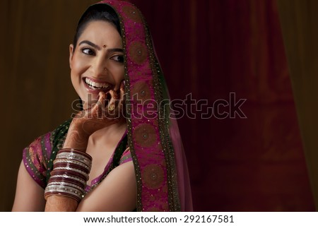 Cheerful young Indian bride looking away - stock photo