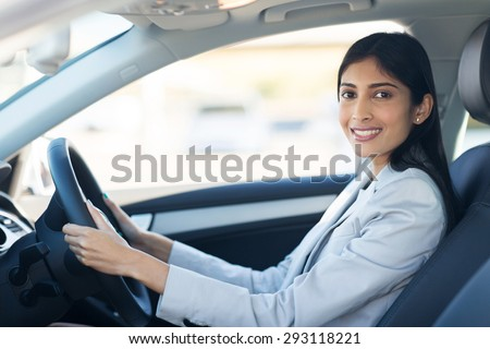 cheerful young indian businesswoman driving a car - stock photo