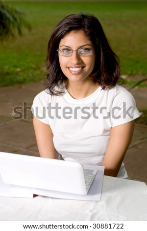 cheerful young indian college student outdoors with laptop - stock photo