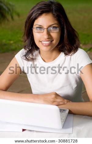 cheerful young indian college student outdoors with laptop
