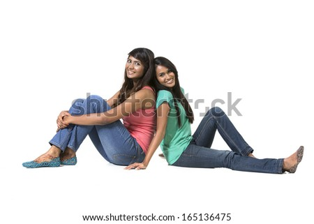 Cheerful young Indian friends sitting with back to each other on floor. Isolated on white background.