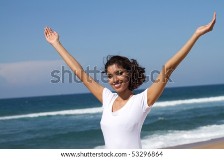 cheerful young indian woman relaxing on beach - stock photo