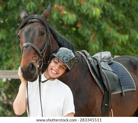 Cheerful young jockey woman  with purebred horse outdoors - stock photo