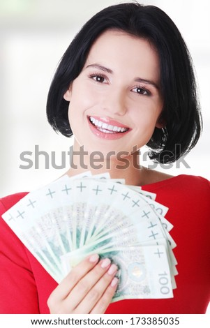 Cheerful young lady holding cash - polish zloty ( pln )  - stock photo