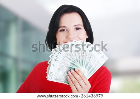 Cheerful young lady holding cash - polish zloty ( pln ) - stock photo
