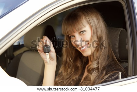 Cheerful young lady sitting in a car and showing the key