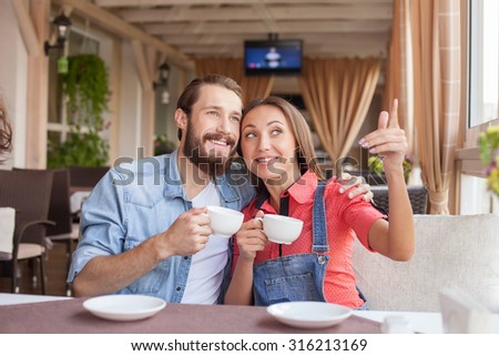 Cheerful young loving couple is dating in cafe. They are sitting and embracing. The pair is drinking coffee and smiling. The girl is pointing her finger sideways with interest - stock photo