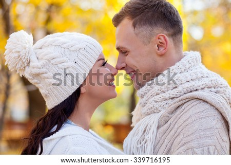 Cheerful young loving couple is resting in the autumn park. They are touching noses playfully and smiling. The man and woman are standing and embracing. They are looking at each other with love  - stock photo