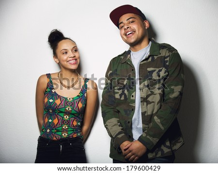 Cheerful young male and female model on grey background. Happy young couple standing together. - stock photo