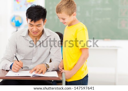 cheerful young male teacher grading school boy's work - stock photo