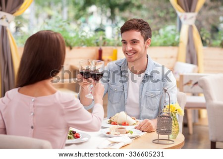 Cheerful young man and woman are dating in restaurant. They are sitting at the table and looking at each other with love. The lovers are drinking wine and smiling. The man is giving a toast - stock photo