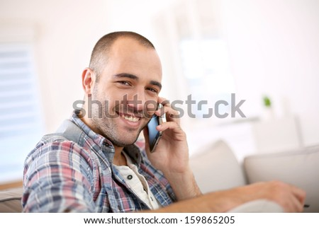Cheerful young man at home using smartphone - stock photo