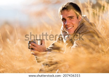 cheerful young man drinking coffee outdoors in fall - stock photo