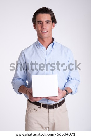 Cheerful young man holding a white box he is holding - stock photo