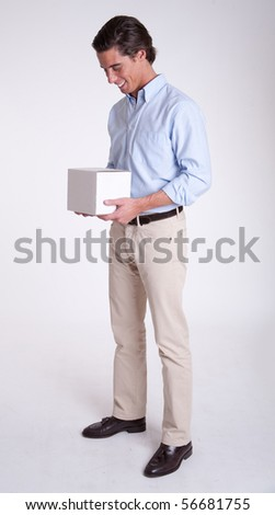 Cheerful young man holding a white box he is holding