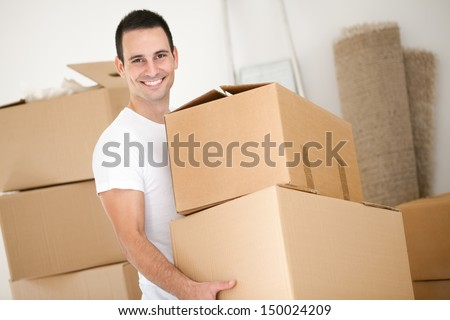 Cheerful young man holding  cardboard box - stock photo