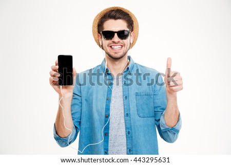Cheerful young man in earphones showing blank screen cell phone and showing thumbs up over white background - stock photo