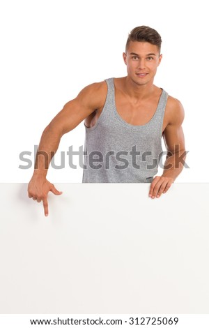 Cheerful young man in gray shirt standing behind white banner and pointing. Waist up studio shot isolated on white. - stock photo