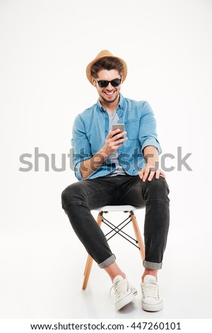 Cheerful young man in hat and sunglasses sitting and using smartphone over white background - stock photo