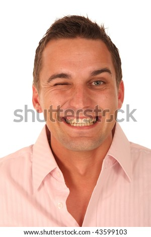 Cheerful young man in pink shirt winking and smiling - stock photo