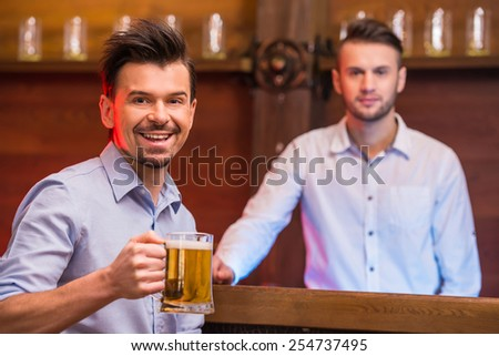 Cheerful young man in shirt with beer while sitting at the bar counter and bartender are looking at the camera. - stock photo