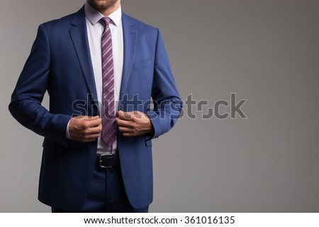 Cheerful young man in suit is preparing for an appointment. He is standing and touching his jacket. Isolated and copy space in right side - stock photo