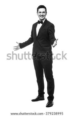 Cheerful young man in suit welcome sign and smiling while standing against white background.Showman concept.