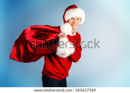 Cheerful young man in warm winter clothing and Christmas cap holding bag with presents.  - stock photo