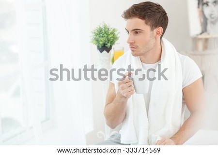 Cheerful young man is drinking coffee and dreaming. He is sitting and looking through the window pensively. The man is holding a cup and a towel - stock photo