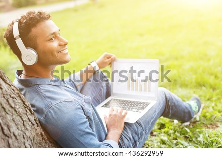 Cheerful young man is enjoying melody in nature - stock photo