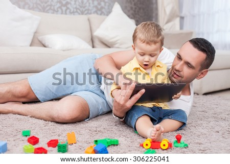 Cheerful young man is lying on flooring near his little son. The boy is sitting on carpet and holding a tablet. The child is looking at it with amazement. His father is smiling - stock photo