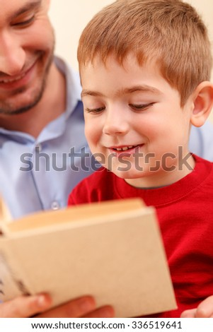 Cheerful young man is reading a book to his small son. They are sitting and smiling - stock photo
