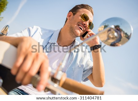 Cheerful young man is sitting on scooter and talking by phone. - stock photo